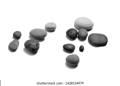 Scattered sea pebbles. Heap of smooth gray and black stones isolated on white background. Rounded rocks