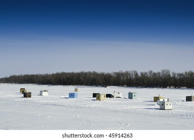 """Scattered shacks used for ice fishing situated on the frozen """"Red River"""" in Manitoba."""