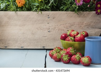 Scattered strawberry fruits in green bowl and juice in blue clay cup on blue table with wooden wall and flower in the background
