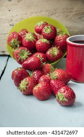 Scattered strawberry fruits in green bowl and with juice in red clay cup on blue table with wooden wall in the background