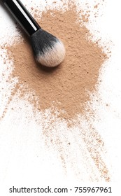 Scattered tan colored facial loose powder and make-up brush on white background. Top view point.