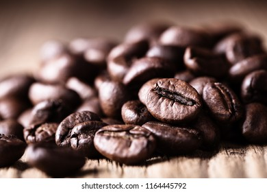 Scattered whole roasted coffee beans on wooden  rustic background. Vietnamese Robusta. Close-up shot.
