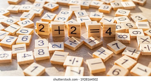 Scattered wooden plaques with numbers and signs. Two by two is four. Teaching material in mathematics, Montessori method. School background. Simple solving concept. Laser cutting and printing on wood.
