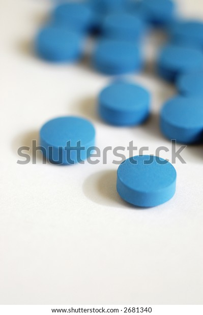 A scattering of blue pills of a psychiatric medication, vertical with copy space