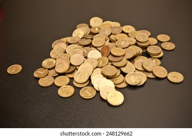 scattering of coins on a black wooden background, shallow depth of field