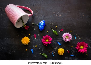 a scattering of herbs and flowers from a fallen pink mug on a black background