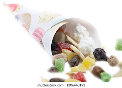 a scattering of a mixture of dried fruits and nuts, a mixture of dried fruits and nuts in a horn, a sweet mixture isolated on a white background