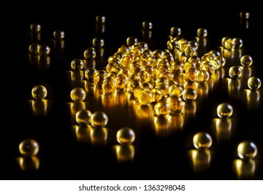 A scattering of yellow transparent capsules on a black background. Vitamins. Fish oil. Omega-3. D3