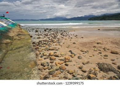Scatttered stones on the beach of Sabang town facing N.and limited to the E.by the concrete wall of the harbor dock-red flag waving. Puerto Princesa Subterranean River Nnal.Park-Palawan-Philippines.