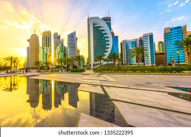 Scenary of Doha West Bay skyline at sunset light reflecting in the water of park in Downtown. Modern glassed skyscrapers of Doha skyline in Qatar, Middle East, Arabian Peninsula in Persian Gulf.