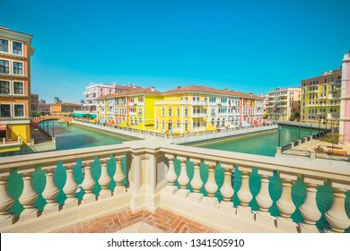 Scenary of Venice at Qanat Quartier in the Pearl-Qatar, Persian Gulf, Middle East. Aerial view of Venetian bridge and canals of picturesque and luxurious district of Doha, Qatar. Sunny day blue sky.
