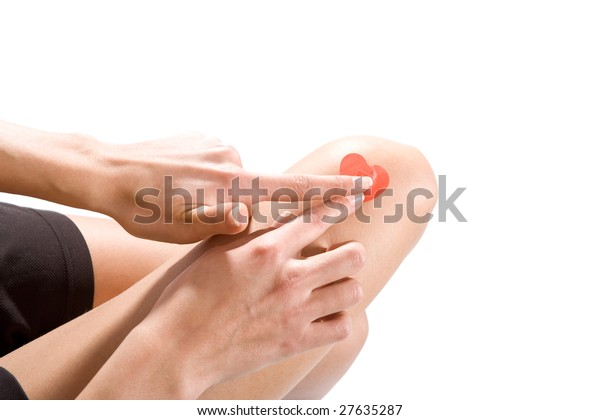 Scene from above - heartshaped plaster is being applied on knee. Isolated on white.