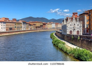 Scene along Arno River in Pisa, Italy, featuring the Gothic marvel Santa Maria della Spina.