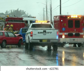 Scene from auto accident on rainy day. There are red emergency vehicles with flashing lights. A sheriff's white pickup truck with yellow lights is at the scene. Two damaged vehicles are being examined