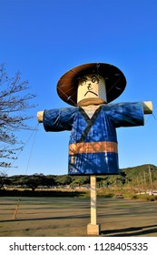 "A scene of a big scarecrow doll. Traditional doll that expresses Japanese characters of ""HENOHRNOMOHEJI"" on the face. Scarecrows are watching over the town."