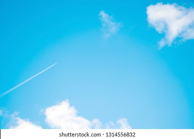 Scene bottom view of blue sky with white clouds moving and make shape as heart, beautiful nature in day time, feel soft and smooth and peacefull and romantic love moment, with trail white smoke .