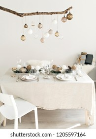 Scene of a bright lit minimalist living room with Christmas decoration and table served for four person. Vintage christmas balls are hanging on a branch, wrapped gifts are on a background.