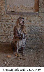 A scene of child poverty amongst children. The child is seen to be situated in a poor unclean environment wearing rags as clothing. Her face reveals sadness and sorrow.