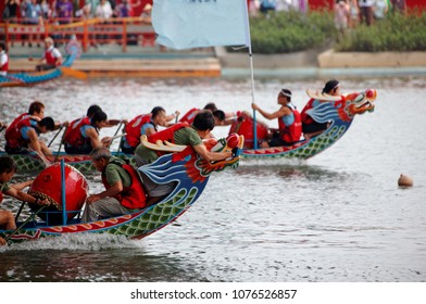 Scene of a competitive boat racing in the traditional Dragon Boat Festival in Taipei, Taiwan, with view of athletes pulling vigorously on their oars and competing strenuously in colorful dragon boats