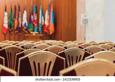 Scene at conference hall with lots of golden chair for attendee to sit and wooden podium and flags in the front for guest speaker to stand