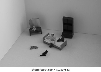 Scene created with miniature toy people. Stereotype of the lonely or crazy cat woman. Lady with many cats in her apartment or house. How many cats is too many cats?