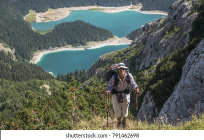 Scene in Durmitor mountains (Montenegro). Woman with backpack against Black Lake background.