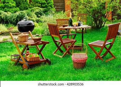 Scene Of Family Barbecue Grill Party Or Picnic On The Lawn In The Backyard At Summertime Weekend.