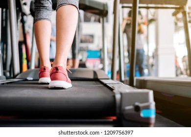Scene in fitness gym. Sneaker shoe of sport girl exercise running on treadmill machine.