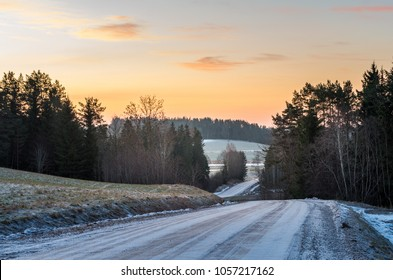 A scene with a frosty winding road, forests and the morning light