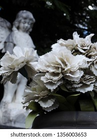 Scene in a graveyard: in the foreground, a vase with some white artificial flowers. In the blurred background, an old stone statue of an angel. Silence and sadness.