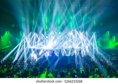 Scene illuminated by beautiful rays of lighting equipment. The concert crowd having fun at the center in the big hall. Television is broadcast live. Many people look towards the stage.