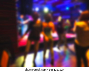 Scene with light, musicians on stage in the rock-cafe. People dancing around the stage. Blur effect.