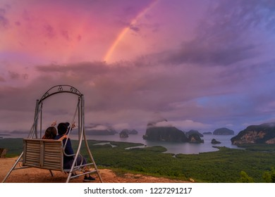 Scene of lovers sitting and pointing to the rainbow over the Fantastic Landscape of samed nang chee view point at the sunrise time, Travel and holiday concept