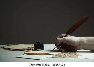 Scene with a man's hand writing a letter or story with vintage quill and old pieces of paper on white table - with copy space for text