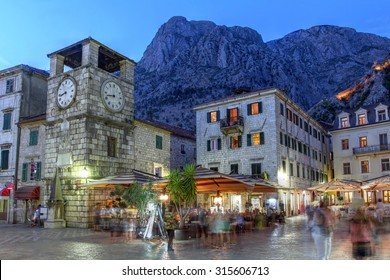 Scene in the medieval town of Kotor, Montenegro at twilight, featuring the Square of Arm and the clock tower near the Maritime entrance gate.