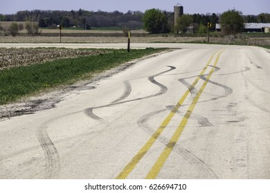 Scene of a near miss perhaps: Rural road with snaky tread marks near an abrupt turn, for themes of safe driving and avoidance, circumstance, suddenness and change of direction