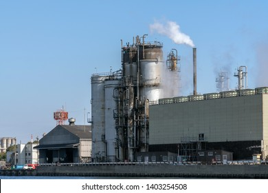 Scene of Oil refinery industial zone beside the river on working hour which have Steam smoke, factory and industry with pollution concept