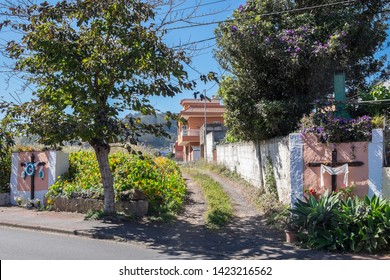 Scene on a rural road with decorated crosses on the exterior walls of estates next to a road on the outskirts of the city of La Laguna, on Tenerife, Canary Islands