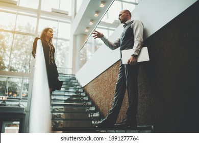 A scene on the stairs of a modern luxury office skyscraper with a selective focus on an actively gesticulating man entrepreneur with a laptop explaining something to his female colleague