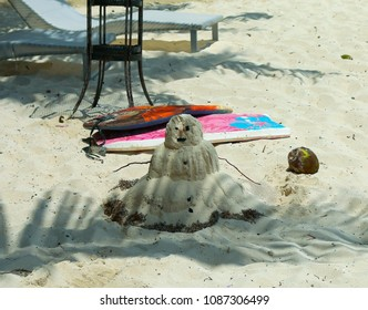 Scene with palm leaf shadow, coconut and snowman made from sand.