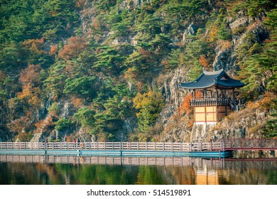 scene of pavilion and yellow trees in mountain and lake, people take a waking along lake