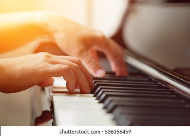 Scene of pianist hands from beside angle playing piano, Photo in warm tone colors. Selective focus.