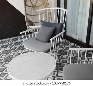 Scene of a porch with furniture.
