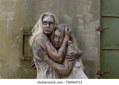 A scene of poverty with two young homeless girls.  They are seen to be situated in a poor unclean environment wearing rags as clothing. Their faces reveals sadness and sorrow in them.