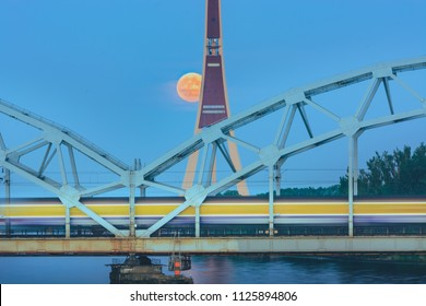Scene of public train crossing river with full moon in background. Latvian television tower and iron bridge in background.