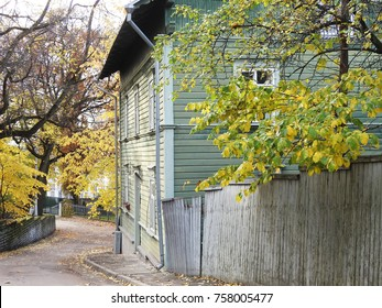 Scene from quiet autumn street with green wooden house and grey wooden fence in Tallinn, Estonia