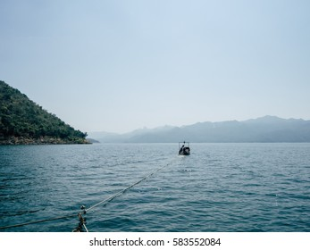 Scene from raft with motor boat pulling around the lake and mountain.
