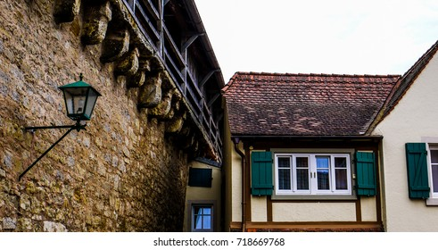 Scene from Rothenburg Ob Der Tauber, showing beautiful painted, timber framed, buildings and the city wall. Taken on a cloudy day.