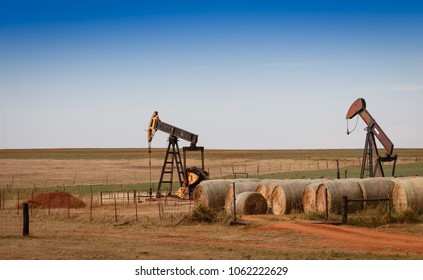 A scene from rural Oklahoma. Oil pumps and hay bales in the prairie.