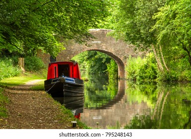 A scene of serenity and reflections, a narrowboat is seen on the still canal waters in the heartland of England, along with a stone arched bridge.